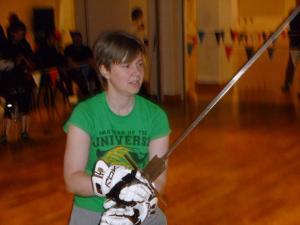 Jo Thomas holding a federschwert, a training version of a longsword